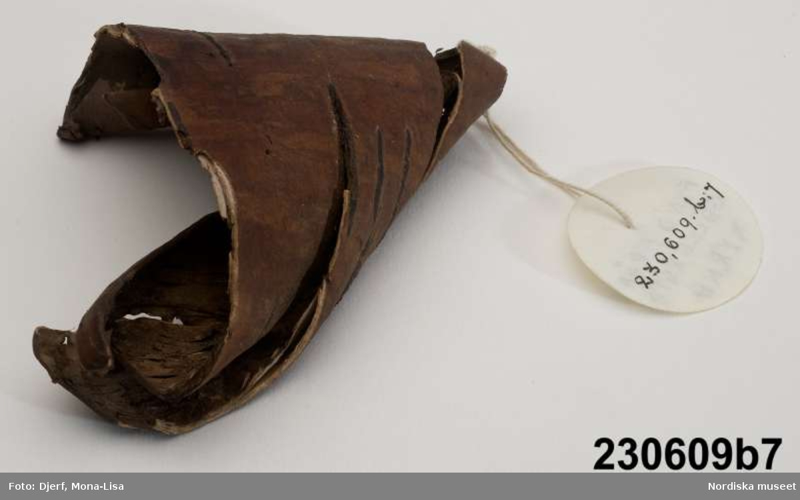 """Huvudliggaren: """"Toffel, fragmentarisk, av brun sammet med lädersula (a1-2). Träfragment (b1-8). Fynd inom resterna av murad grav i Gällestads kyrka."""""""