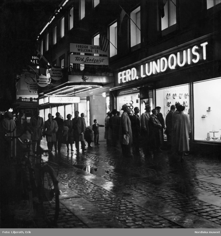 Göteborgs centrum kvällstid. Människor tittar i varuhuset Ferdinand Lundquists skyltfönster
