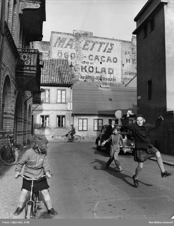 Barn som leker på en gata i Malmö. I bakgrunden reklam för Mazettis ögonkakao.