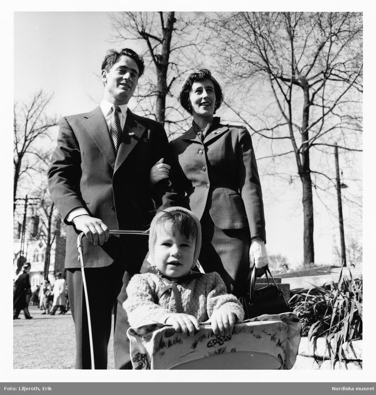Familj med barnvagn på promenad i Pildammsparken, Malmö. Kvinna och man i armkrok. Mannen skjuter barnvagnen, där barnet sitter, framför sig.