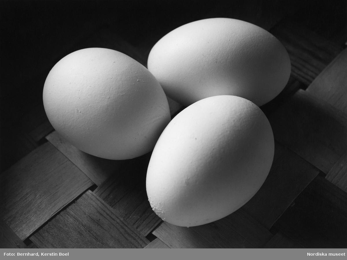 Ägg. Tre stycken ägg på ett flätat underlag.