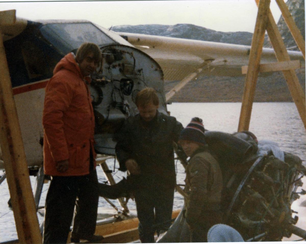 Fly ved vannkanten, LN-KCQ. DHC-2 Beaver. Motorbytte. 3 personer ved flyet.