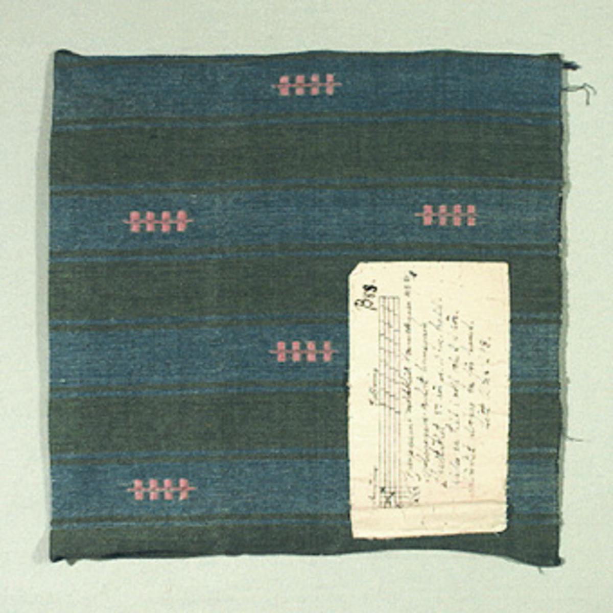 Vävprov ämnat för möbetyg vävt med bomulls- och lingarn i färgerna blått, grönt och rosa. Vävtekniken är korskypert med mönsterinplock. På vävprovet finns påsytt en vaxad tyglapp med vävinformation. Vävprovet är märkt B88.