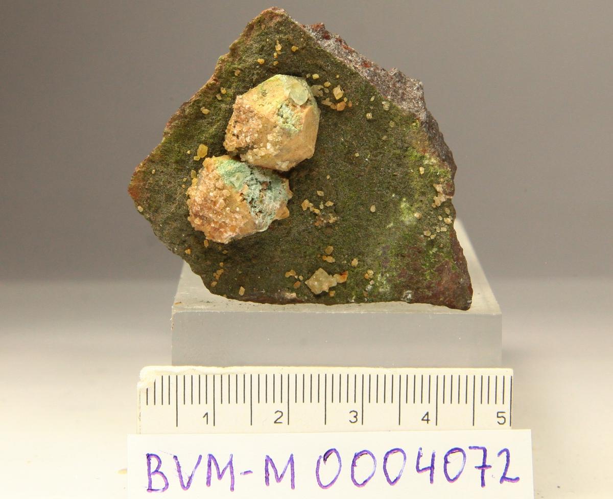 Mikroklin pseudomorf etter analcim. Små kalsittromboedre på mikroklin. Feiring Bruk, Lørenskog.