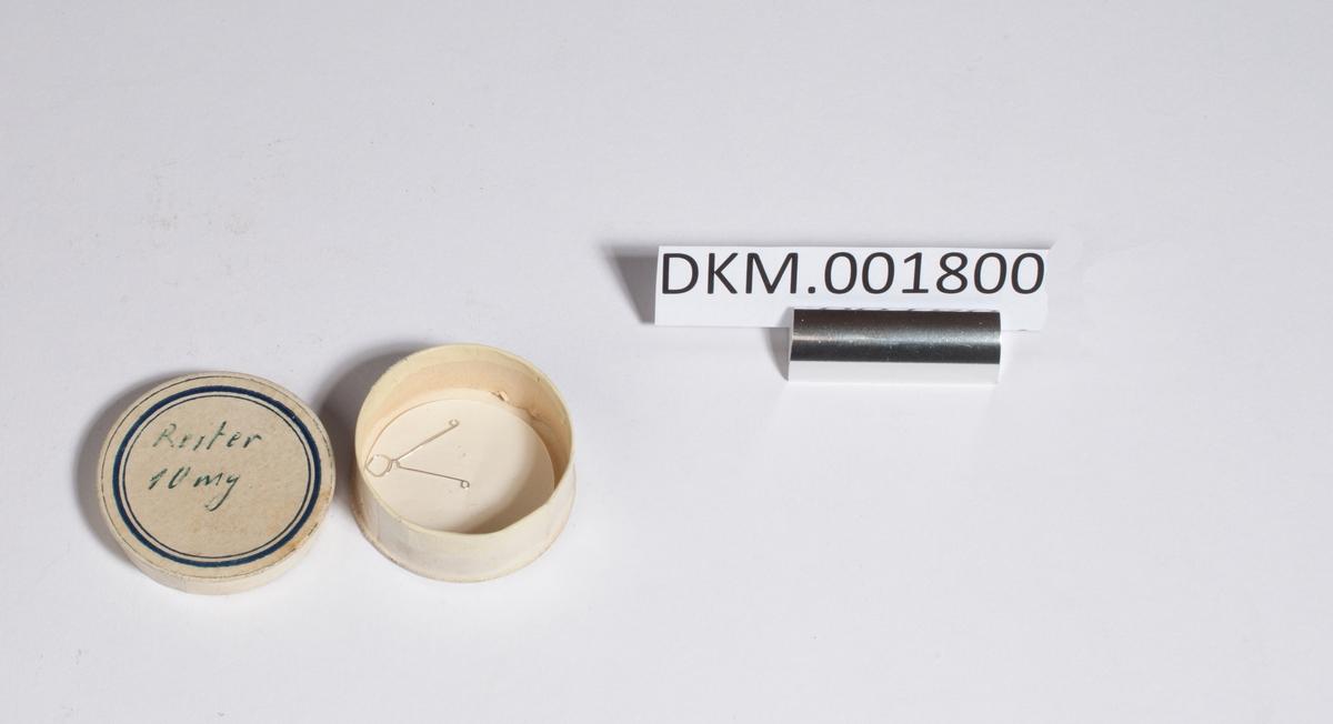 En tynn metalltråd som er bøyd på midten og tvinnet ett par ganger rundt seg selv, den ligger i ett rundt pappetui.