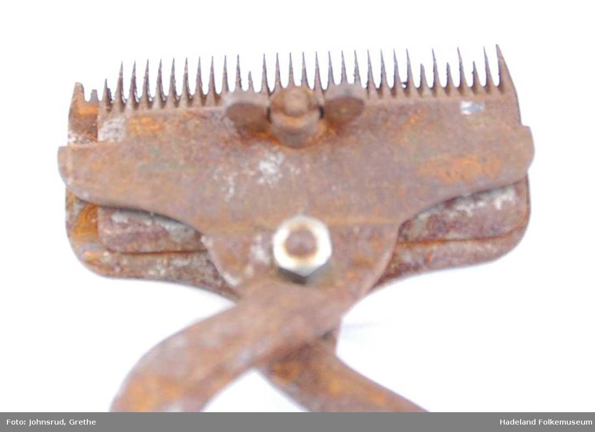 To deler som er skrudd sammen. Saksekjeften består av to kamformede kniver som beveger seg motsatt i sideretningen.