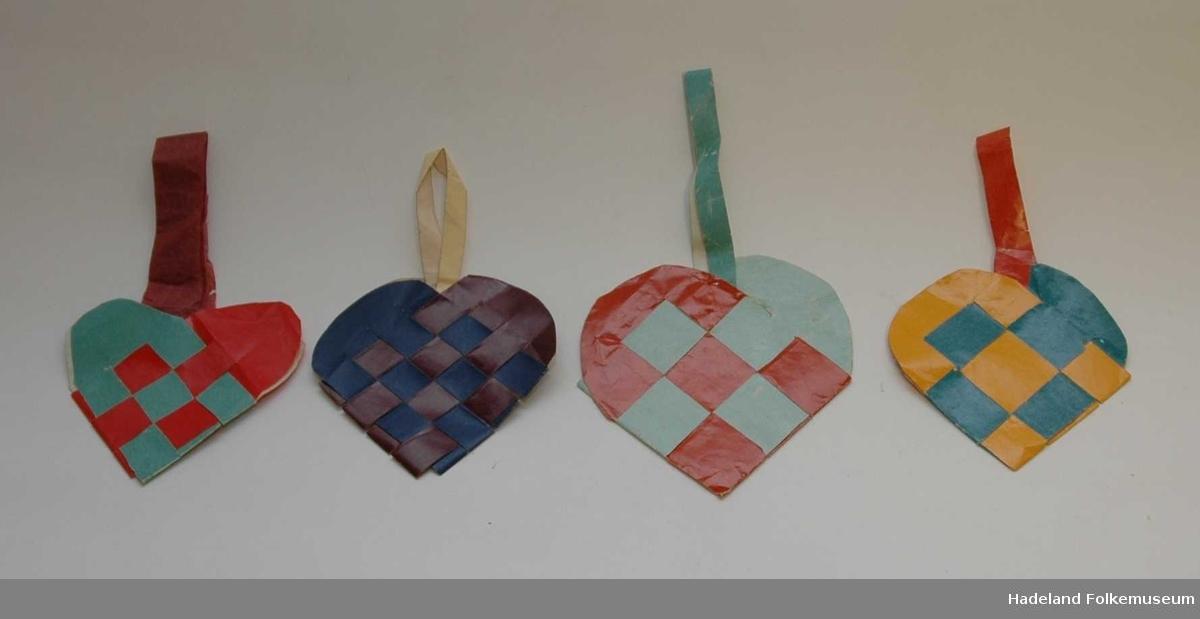 Papir, hjerteformet, 9 ruter, flettet. Lange hjertebuer. Hank i silkepapir er limt på.   Foto: Nr. 1 fra venstre