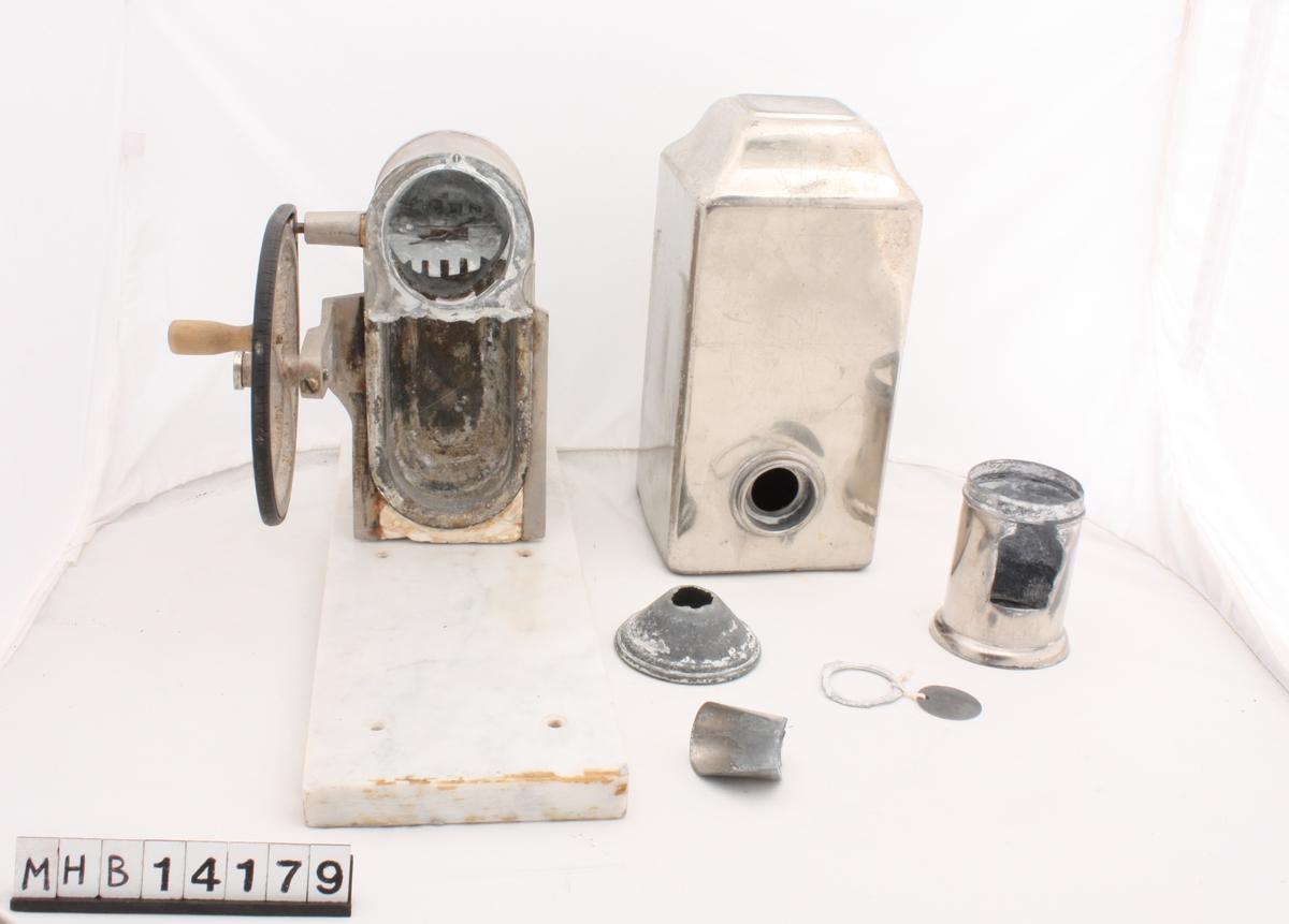 Barberskummaskin i 6 deler. Hoveddelen består av en metallinnretning festet på en rektangulær marmorplate. På den ene siden av metallinnretningen er det et hjul med håndsveiv. Ytterst oppå metallinnretningen er en sirkulær åpning. En sylindrisk del med kan settes ned i denne. Til den sylindriske delen hører til en sirkulær metallramme og en metallmunning. En rektangulær metallboks med hull i siden plasseres oppå metallinnretningen på marmorplate. I tillegg hører en traktformet metalldel til maskinen.