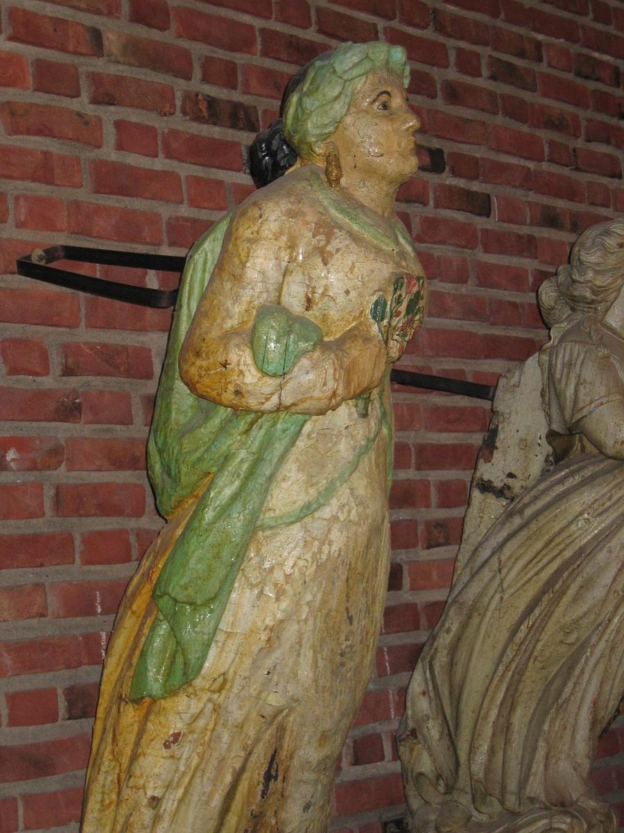 En klassisk gallionsfigur, venstre arm ned langs siden, høyre arm bøyd med en blomsterbukett i hånden mot brystet. Sort hår, hvit kjole med grønn kant, blomster i høyre hånd mot brystet.