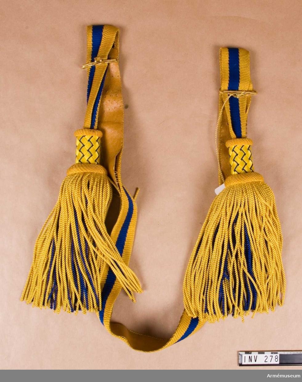 Gjort av blått och gult tvinnat silke i trikå. De yttersta ränderna är gula, c:a 15 mm breda, den mittersta randen är blå i samma bredd. Skärpet är fodrat med ljust läder. Den stela övre delen av tofsen är flätad över trästomme. Dvs. gult silke spunnet över pappremsor, 6 mm breda, korgflätade tillsammans med blå snodd av silke. Stommen fortsätter något under övre delen av tofsen för att föra ut denna. Stommen är då något vadderad och överklädd med blå satin. Tofsar av tvinnat, snott silke, består av ett inre lager blå silkessnodd och ett yttre lager gul silkessnodd. Gulmetallspänne försett med hakar för att reglera skärpets vidd Rulla 1916.