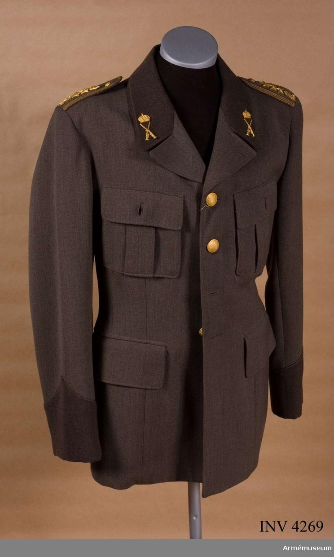 """Redan 1939-06-28 inlämnades av dåvarande arméchefen förslag t fältuniform m/1939, permissionsuniform m/1939 försedd m mattförgyllda tjänstetecken samt paraduniform. Den 6 okt 1939 meddelades att pga det utrikespolitiska läget kunde fredsuniform (permissions-/parad-) ej fastställas. Fältuniform fastställdes 1939-09-22, se AM 3803. Årsskiftet 1951-52 aktualiserades tillverkning av permissionsuniform. De begynnande svårigheterna  textilindustrin föranledde statsmakterna att vidtaga åtgärder f att hålla tillv. i gång. I april 1952 meddelade arméchefen de militära myndigheterna om planerna på ny uniform. En konferens ägde rum 1952-04-18--04-19 då olika modeller visades. Denna modell vann mest gehör. Av gråbrungrön kamgarnsdiagonal m ärmuppslag och krage i mörkare färg. Tjänstetecken i mattförgyllt utförande. H M Konungen (Gusav VI Adolf) och försvarsministern (Torsten Nilsson) godkände dock ej de mörka inslagen på rocken men i övrigt helt gillande. Statsmakterna hade nu anvisat medel, 49,9 Mkr, f tillv. av uniformstyg m m. För att möjliggöra att de värnpliktiga skulle kunna tilldelas uniform av diagonaltyg vid inryckning t 1.a tjänstgöring 1953 samt att snarast tillföra textilindustrin beställningar var det nödvändigt att snabbt fatta beslut om färg på tyget. Beslut fattades 1952-04-28 om mörkt tyg t byxor. Uniform m/1952, se AM 3810, fastställdes 1952-07-02. Märkt på fodret i ryggen m stämpelfärg tre kronor. På V framstyckets insida vävd etikett m firmanamn """"Örnkläder"""", adress okänd. På innerfickans insida vävd etikett """"MALSÄKRAD"""".  Till skillnad från den fastställda modellen är knapparna löstagbara."""