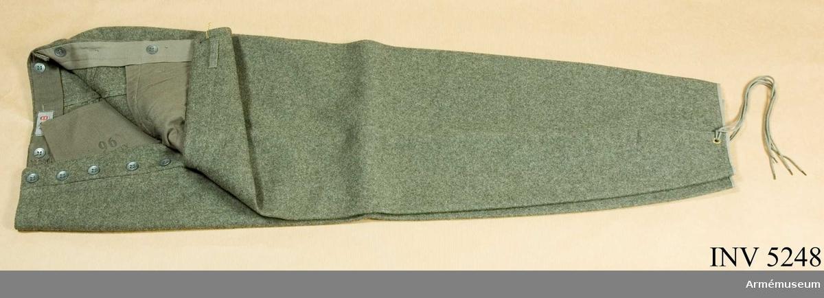 Kläde. Storlek: 96. Av gråbrungrönt kommiskläde av ylle, vida över  säte och knä, avsmalnande nedanför knäet, med anordning för tillslutning nedtill på byxbenet samt med slejfar i livet. På  linningens insida och i jylfen kompositionsknappar. På  linningens insida märkt: ACB Stockholm (Arméns centrala  beklädnadscentral) 96 1946 tre kronors stämpel. På en pappersetikett märkt: Byxor fält m/1939 Storlek 96 Bunt nr 3682  FFV 25759 46. 50000 .