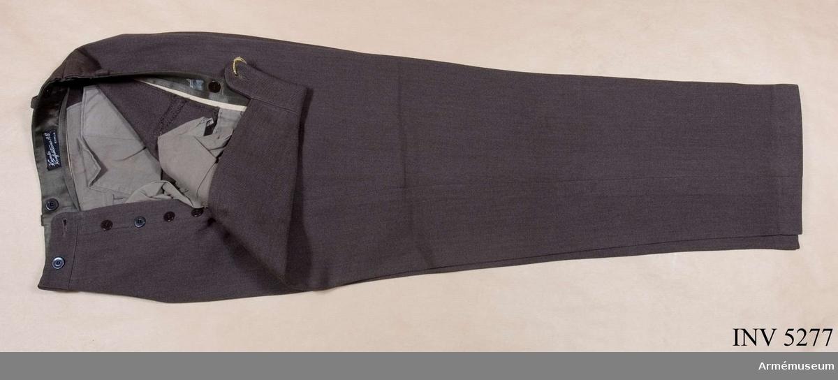 Storlek: B 46. Mörkt gråbrungröna byxor, mörkare än vapenrocken, tillverkade i yllediagonal. Jylfknäppta med hällor i linningen. Sidfickor ooh en bakficka. Daglig dräkt.
