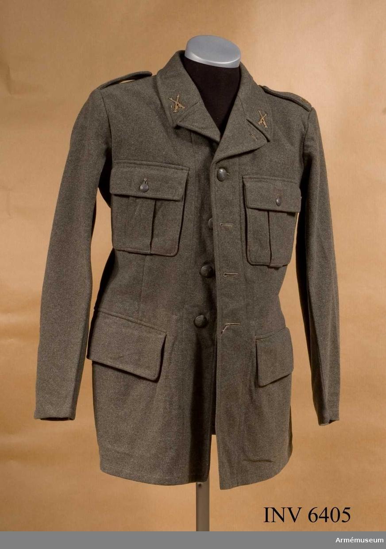 Stl 96. Av samma snitt som uniform m/1939. Daglig dräkt av gråbrungrönt tyg. Bäres till gråbrungröna byxor. Tjänstetecken mattförgyllda.