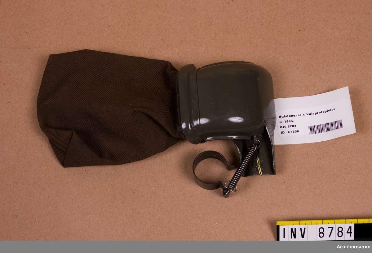 Hylsfångare t kulsprutepistol m/1945.Märkt L & L 1958. Höjd med påse 230 mm.Hylsfångare består av: Hylsavledare, klämring, fästklack och hylspåse av väv. Se Soldatinstruktion för armén Materiel 1969. sid. 56-57.