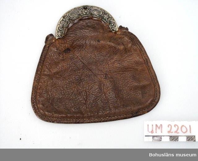 Ur handskrivna katalogen 1957-1958: Plånbok av skinn m. mässinglås Mått: 14,2 x 15,3 x 1 cm. beslaget utsirat; läderet torkat och ngt. rispigt.  Lappkatalog: 37