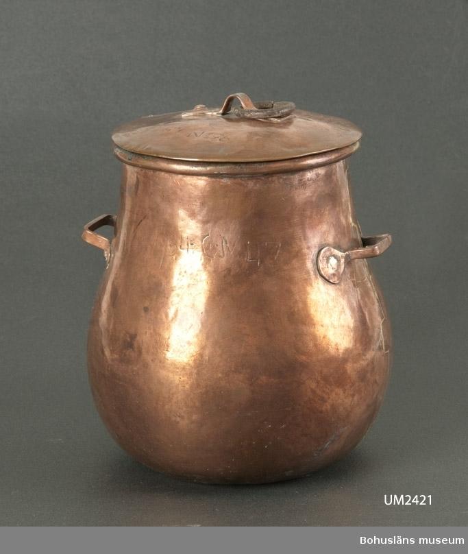 """Militärt dryckes- och kokkärl av koppar, runt och bukigt, med vid mynning, två hänklar och lock. Inuti rester av förtenning. Bärhandtag av läder eller metall saknas. Ett antal inristade siffror och bokstäver på krukan. På locket inristat F:C No 26  Ur handskrivna katalogen 1957-1958: Flaska nr 26 Flaskan a) H. 18, D (upptill) 13 cm; m. 2 öron av koppar; locket b) D. 13 cm; m. ring av järn upptill. Upptill """"F:C No 26"""".  Litteratur: Rosenström, P. H.: Bulkruka och kokkittel i fält. Kapitel ur boken Gammal koppar. Om kopparslagare och kopparsaker. ICA-förlaget. 1962, s. 72 - 75."""