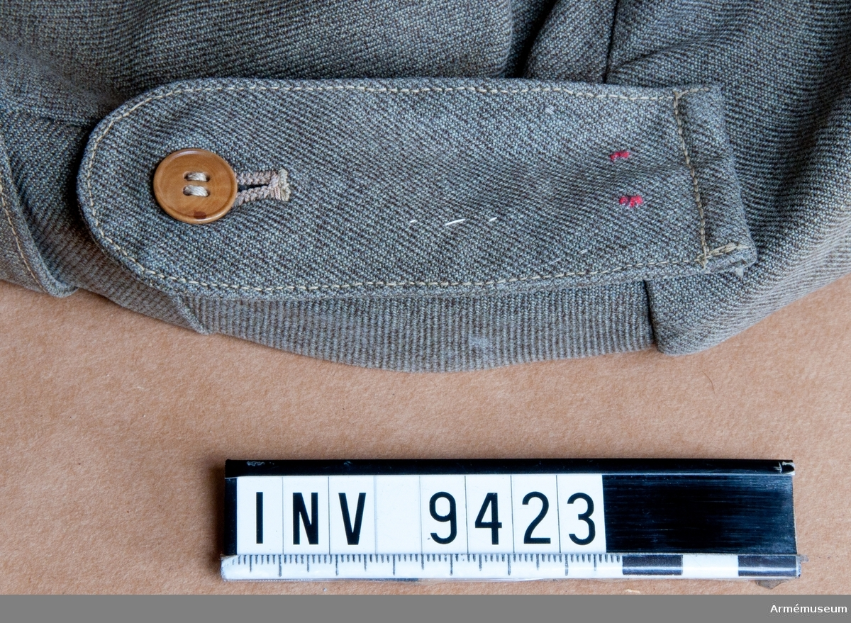 Två tampar sitter fäst på kappan i vilka axelklaffen sitter fast. Axelklaffens övre bredare del har ett knapphål och knappen sitter under.