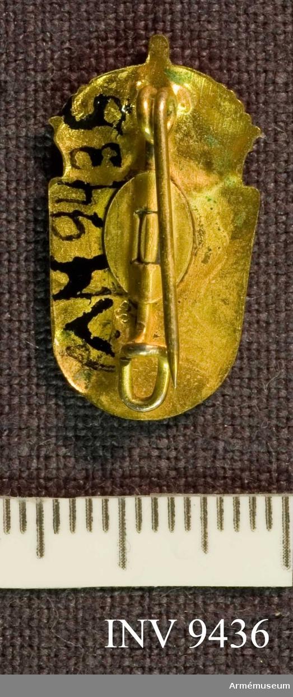 Samhörande nr är 9421 - 9438. Civilförsvarsmärke i guld, SLK. Ett förgyllt märke, troligen tillverkat hos Sporrong. Ingen märkning finns synlig. Framsidan visar två korslagda värjspetsar vilande på en sköld, krönt av en kunglig krona.