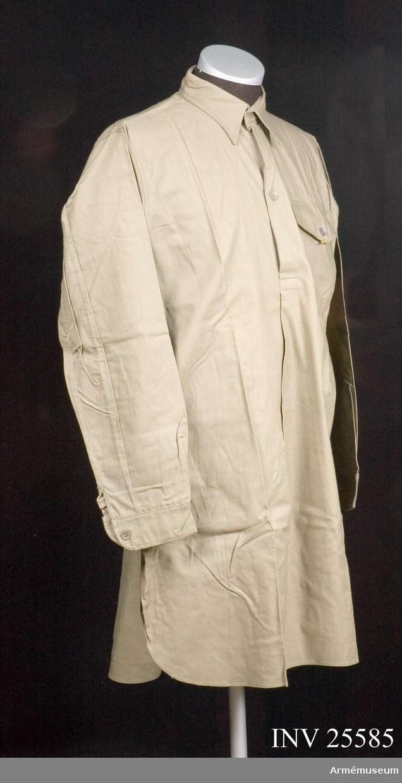 Storlek 38.Gråbrungrön skjorta i bomull med fast krage och linning vid ärmen samt en västerficka. Knäpps i sprund med två kompositionsknappar samt en dito på ficklocket.  Märkt på  kragens insida: Engers 38 20 K 3.