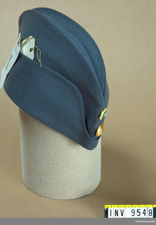 """Båtmössa, typ belgisk FV-modell.Av gråblått ylletyg. Har grått konstsidenfoder och ljusbrun svettrem. Mitt fram """"trekronors""""-knapp i mattguld och det svenska nationalitetsmärket m/1941."""