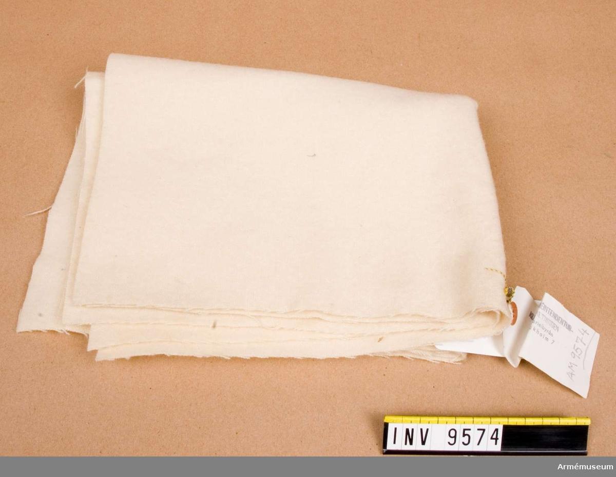 """Vita yllelappar tillklippta av vitt ylletyg. Används vikt runt foten. Gåva från FMV i Solna. 1988-03-04 noteras att på förlagan är """"antal"""" angivet till 1 och """"samhörande"""" till 3."""