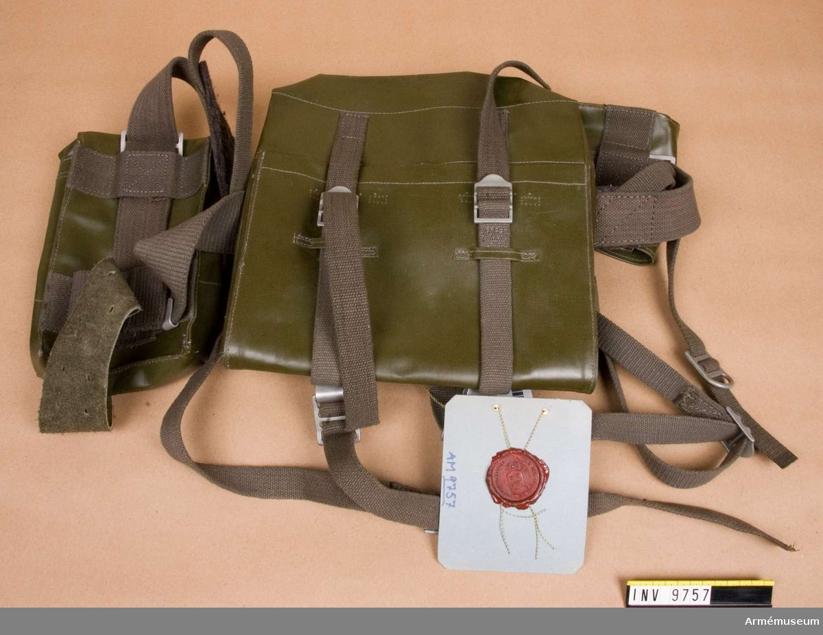 Stridssele m/1960, sats. Av olivgrön vävburen plast med gröna cordhängslen. En stor väska och två mindre.