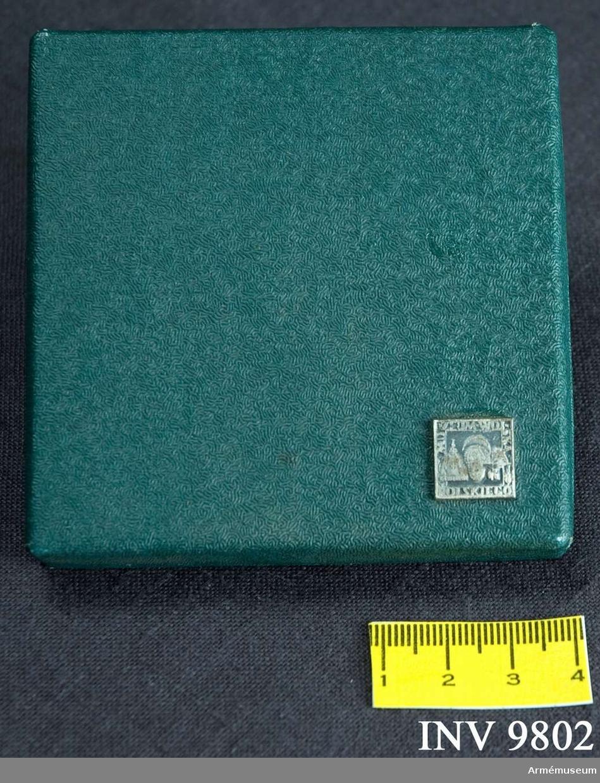 Ask av grön klot tillhörande AM.009801. På lockets nedre högra hörn är fästad en miniatyr av inneliggande minnesplakett. Insidan är klädd med svart sammet och har i botten en för plaketten avpassad nedsänkning.