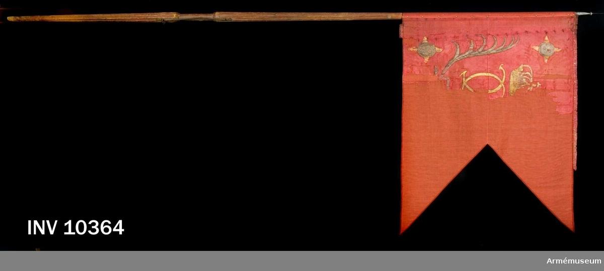 Grupp B I.  Fanan är från tidigare delen av Karl XI:s regering och torde ha förts av Rikskanslerns dragonregemente. Duk av röd taft varå målat lika på båda sidor Karl XI:s  namnchiffer, dubbelt C under kunglig krona, allt i guld, kronan prydd med stenar i rött och grönt, det hela har förr inneslutits av två nedtill korsade och med rosett i silver hopknutna,   lyrformigt böjda palmkvistar i silver och grönt, av vilka blott den ena finns i behåll. I de inre hörnen (förut även i uddarna) fyrkulor i silver med sju synliga hål, ur fyra av vilka utslår gyllene lågor. Ursprungligen löpte runt kanten en 2 cm bred frans, varav numera återstår endast en ringa del. Duken fäst vid stången med skinnband och förtenta järnspikar.  Dukens ursprungliga höjd 104 cm, nuvarande bredd 77 cm och från tungan till stången 134 cm.Stång av furu, ovan och nedom greppet åttasidig med en reffla på var sida, målad röd, försedd med bärring, löpande på ovanligt lång, nedom greppet räckande krampa. Längd: total 339 cm, till  greppet 111 cm, greppet 19 cm och till duken  99 cm. Diameter  upptill 2,8 cm, nedom duken 4 cm, ovan greppet 6,5 cm och i  greppet 4 cm.Spets av järn, i ett stycke, med spiralrefflad platt kula i övergången till det lilla, enkelt spjutformade bladet. Längd 18 cm.