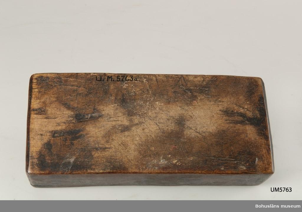 Rektangulär låda, uppdelad i två parallella fack med varsitt skjutlock upptill. Målat med mörkt röd färg. Inuti ett av facken finns fragment av fnöske.  Litt.; Gjaerder, Per, Esker og tiner, C. Huitfeldts förlag, Oslo, 1981, s. 48-50.  Ur handskrivna katalogen 1957-1958:  Trälåda m. två skjutlock a) L. 22,5 Br. 9,7, H. 5,3 cm, rödmålad; m. 2 fack, under m. ett skjutlock b) och c); deras L. 21,2 cm, Br 4 cm.  Lappkatalog: 84