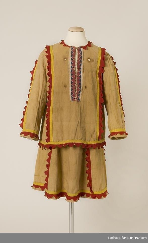 Kjol och blus av gulbrunt bomyllstyg med garneringar av gula band, klippta (taggiga) röda bomullsremsor. Garnering i halsöppning av bomullstyg i rosa,vitt och blått. Använd vid lek och teaterföreställningar i Carl och Berta Wilhelmsons familj.  Uppgifter enl. Thomas Lagerman (1929-2008): Dräkten låg i utklädningslåda i ateljén i villan i Fiskebäckskil. Användes av Thomas själv och andra barn.