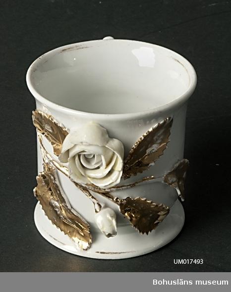Vit mugg med öra. På utsidan dekor i form av skulpterad gulvit ros och knopp samt flera blad, vilka också är förgyllda. Gulddekoren bortnött på flera ställen. Tillverkade i England? Troligen brukade i Dalsland eller Tidaholmstrakten. Inköpta i par.