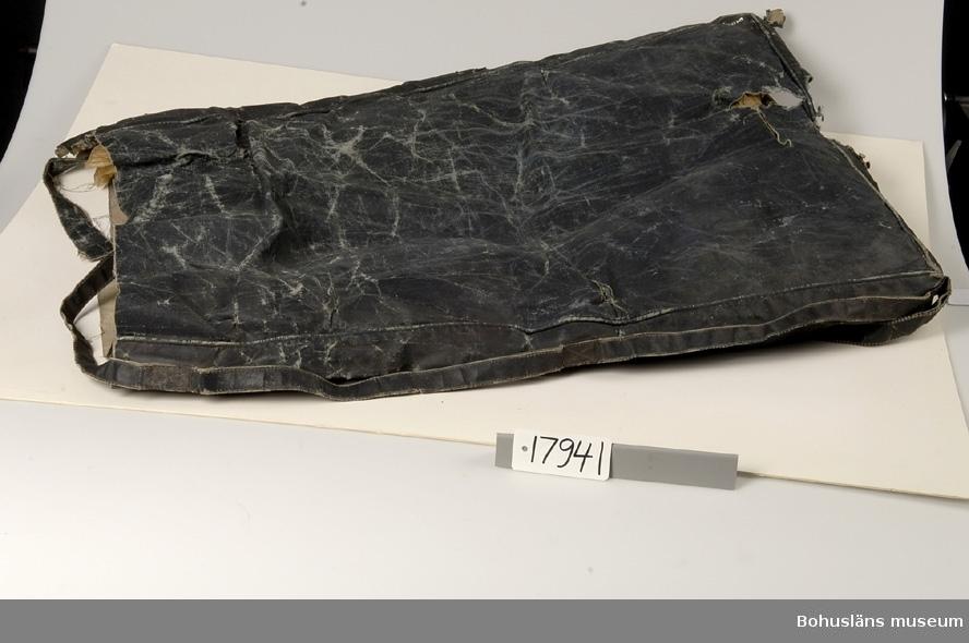 Rektangulärt och svart. Längsgående band på sidorna. Har troligen varit ett överdrag till en dyna innan det gjordes om till ett förkläde. Slitet.  Ingår i redskapsbestånd ur sjöbod från Hällsö, Havstenssund, Tanum sn. Se UM17521.