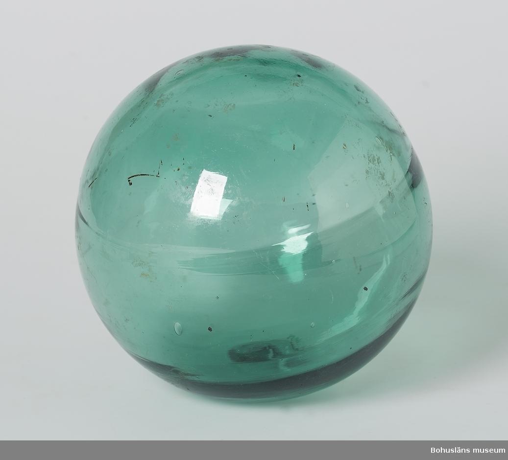 """Grön glaskula. I proppen för puntelns plats inpressat: """"P.C.F"""" och två plus.+"""