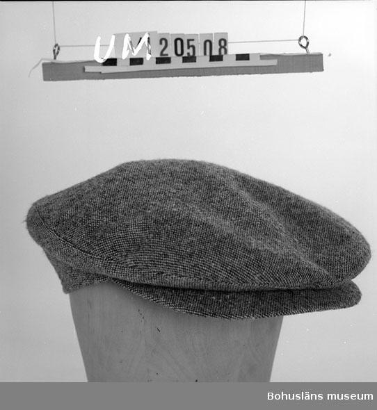 """Gråmelerad keps med grovt konstsidenliknande foder. Troligen från 1930 - 1940-talen. Denna typ av keps kallades """"sixpencer"""" eftersom den ofta inköptes i Englad för """"six pence"""" av fiskare och sjömän. Se Information."""