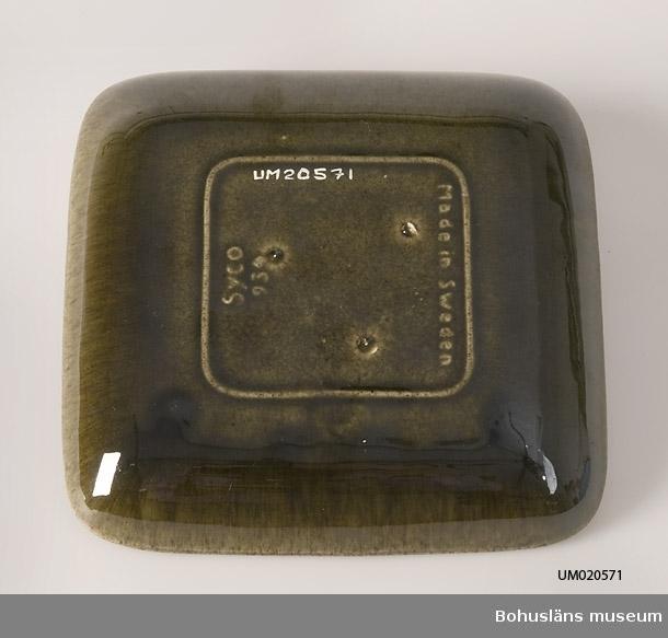 """Fyrkantig grönglaserad tallrik med uppvikt bräm som utan markering över går till spegeln. Märkt i botten med signatur i relief: """"SYCO 934 Made in Sweden."""""""