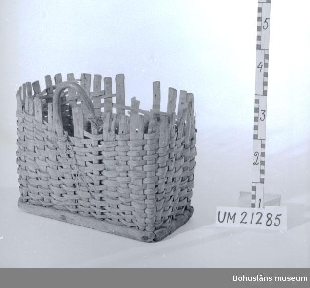 594 Landskap BOHUSLÄN  Rektangulär korg med botten av en bräda. På den ena långsidan är det det ett handtag. Korgen är söndrig i kanterna.  Omkatalogiserat 1997-02-19 GH.  UMFF 8:5