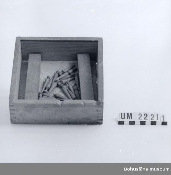 """594 Landskap BOHUSLÄN  Kvadratisk trälåda med zinkade hörn till vilket hör 19 stycken utsnidade """"lamm"""" och 2 stycken """"rävar"""". I lådan ligger också en träkon, troligtvis till ett Fiaspel eller liknande, en svart tärning med vitmålade prickar samt en träbit alla har samma UM-numrering som rävspelet."""