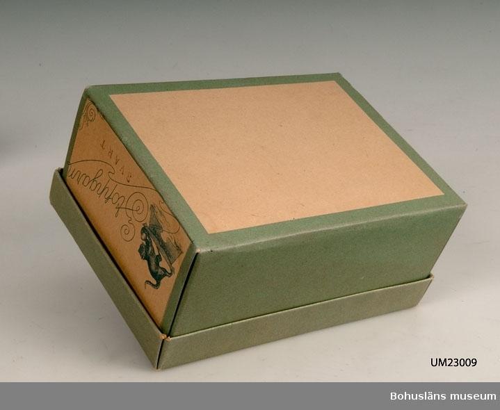 """594 Landskap BOHUSLÄN  Låda med lock i svagt grönfärgat papp. Firmamärke på lock och en gavel i vitt, blått, rött för: """"Aktiebolaget Werner & Carlström. Stoppgarn."""" Innehåller sekundärt en vit och en svart trådrulle. Ur affärens varusortiment."""