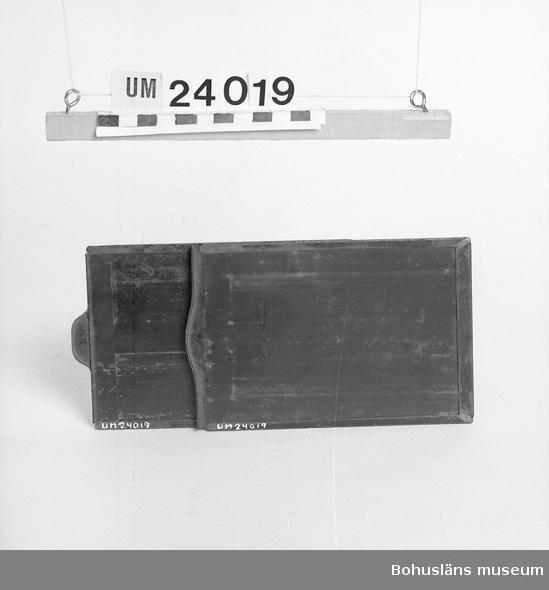 """För negativ. Svart plåt.  På ena sidan påklistrad grön lapp med svart text: """"Achtung! Panchromatisch! Grünes Licht!"""". Uppgifter om ägare och kamerautrustning se UM024016."""