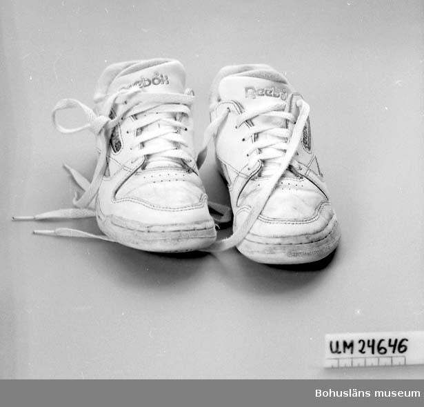 """Landskap BOHUSLÄN  Vitt läder, ljusgrönsa sidoränder av konstmaterial. Vit gummisula. Vita skosnöre. Insidan klädd med vit textil. """"Reebok"""" står på 5 ställen på var sko; under sulan, på sulans sida, på tungan, på sidostycket och baktill. På insidan skon finns en etikett av textil med texten: """"8 USA 6 UK 39 EUR MADE IN INDONESIA RIOI GIA FABRIQUE EN INDONÉSIE 6-3145"""".  Insamlade i samband med dokumentation av Havsbadsrestaurangen, Lysekil, sommarsäsongen 1991. Se museets arkiv."""