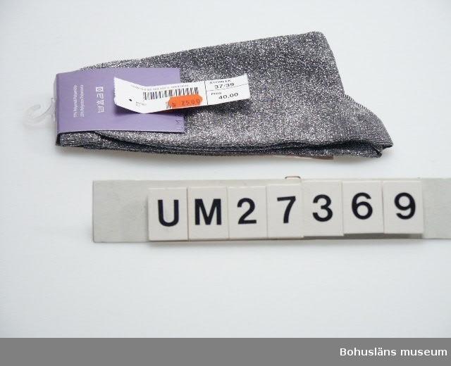"""Förpackning med knästrumpor i silverlurex. Storlek 37-39 i  obruten förpackning. På denna står bl a: """"2000 BY LINDEX"""". Oanvända. Inköpta på Lindex i Uddevalla för 25 kronor, reapris, (nedsatt från 40 kronor).  För information om Millennieinsamlingen, se UM27360."""