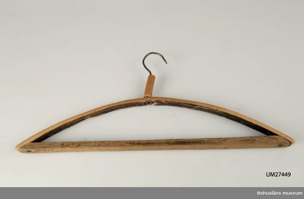 Klädgalge, hemtillverkad med övre delen av ett återanvänt tunnband av ene, krok av kallhamrad järntråd. Intagen till samlingarna som exempel på återbruk. Okänt varifrån galgen ursprungligen kommer.