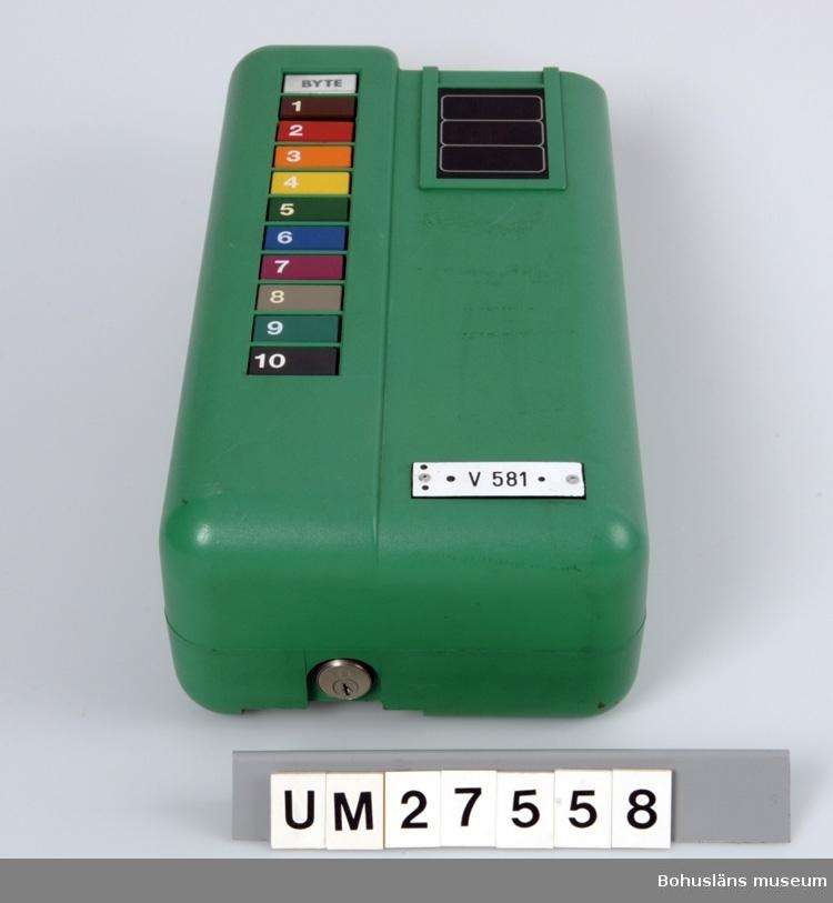 Stämpelmaskin i grön plast (UM27558:1) med två vidhängade nycklar samt en  upphängningsplåt i rostfritt stål (UM27558:2). På framsidan tio knappar i  en lodrätt rad märkta 1 till 10 samt en knapp märkt BYTE.
