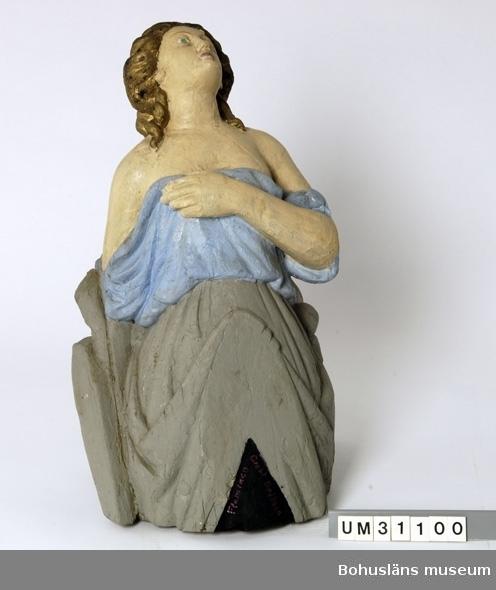 """Föremålet visas i basutställningen Kustland,  Bohusläns museum, Uddevalla.  Galjonsfigur från mitten av 1800-talet föreställande kvinnofigur iförd en löst draperad klädnad som bildar böljande veck.  Kvinnan blickar mot skyn, har en uppsatt frisyr med stor knut i nacken och nedfallande lockar vid öronen, nakna axlar och hon håller klänningens överdel med vänster hand över bröstet. Baksidan är  delvis obearbetad. Figuren är skuren ur ett stycke trä, krederad och bemålad. Nuvarande bemålning är med största sannolikhet utförd av C G Bernhardson med håret i guld, klänningens överdel ljusblått, nederdelen grå, baksidan och en del av framsidans nederdel svart. Nertill på galjonsbildens framsida har Bernhardson skrivit med röda bokstäver:  """"Flamingo Great Britain"""", troligen namnet på ett fartyg, kanske det som galjonsbilden en gång hört till. Uppgifter saknas om fyndomständigheter. Upphängningsögla på baksidan med nylonsnöre. Torrsprickor, färgbortfall som målats över. Bernhardson förvarade galjonsfiguren i farstun till sin ateljé. Hela hemmet var ett museum och i denna del fanns flera maritima föremål. I farstun förvarades också bl. a. trävettar UM31101-UM31108, rorkult UM31115, skansbord UM31119, sjöstövlar UM31124, blosslampa UM31135.  Litt.: Hallén, Tore, Rüster, Reijo, """"Galjonsbilder"""", Rabén & Sjögren, 1975. Vissa sidor finns kopierade och förvaras i bilagepärm, UM2659.  Se även fotodokumentation av Bernhardsons hem under UMFA53175:1-14, UMFA53406:1-31,  UMFA54370.  Den bohuslänske folklivsmålaren Carl Gustaf Bernhardson (1915 - 1998) ägnade stora delar av sitt liv åt att skildra kustbornas villkor, levnadssätt och föreställningsvärld. Han gjorde det i målningar, böcker, uppteckningar och ortnamnskartor och har efterlämnat ett unikt material, en guldgruva för var och en som är intresserad av det gamla Bohuslän. Carl Gustaf Bernhardson föddes 1915 i Grundsund på Skaftö i mellersta Bohuslän. Fadern, Martin Bernhardson, var fiskare på egna kutten """"Welfare"""", modern Lydia v"""