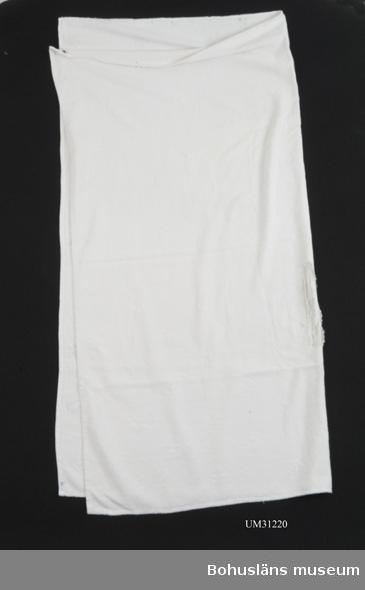 Stor kvadratisk handduk av vit frotté med en invävd figur strödd över tyget. Slitna kanter, revor, flera hål.