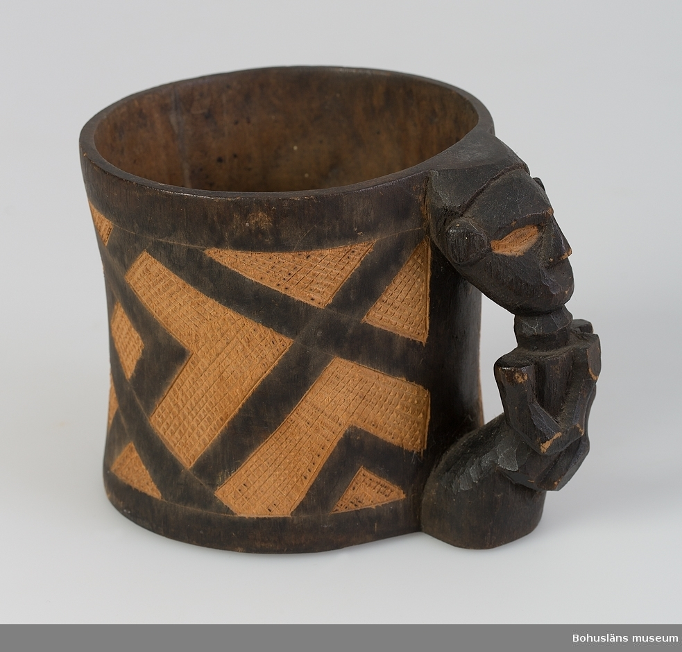 """Text till webbutställning """"Från när och fjärran"""" presenterad på Bohusläns museums hemsida år 2009 - 2013: Mugg täljd ur ett trästycke med utskuret rombiskt mönster, handtag i form av en människofigur, delvis mörkpatinerad yta; höjd 10,2 cm. Föremålet är tillverkat av kuba, en folkgrupp, i Kasai-området, Kongo. Kuba förvarade ofta sina nyttokärl hängande på väggarna i husen.  Mönstren liknar de som användes i deras broderier. Även i flätade arbeten samt på keramik finner man liknande geometriska mönster. Gåva av sjökapten Elmer Göransson år 1961.  Uppgifter om givaren Under sin 30-åriga vistelse i Belgiska Kongo skötte Elmer Göransson (1872-1964) under många år transporter på landets floder. När han år 1932 avslutade sin tjänstgöring var han både skeppsfartygsinspektör för hela den belgiska flottan i övre Kongo, t. f. chef för hydrografiska tjänsten samt hamnkapten i Leopoldville. Han var samlare av bl.a. vapen, textilier och träkärl. I omgångar från 1919 skänkte Göransson afrikanska föremål till Uddevalla museum. Han kom att bli en av museiföreningens hedersledamöter. Vid sin bortgång 1964 var han bosatt i Kungsbacka.  Artikel i Bohusläningen från måndagen den 1 november 1937. """"Vittberesta bohusläningar berätta. Upplevelser under 30-årig vistelse i Belgiska Kongo. Kapten Elmer Göransson. Folk och sedvänjor under ekvatorns glödande sol."""" _______________________________________________________________________  Kontinent: Afrika. Ur lappkatalogen: Trämugg, h. 10 cm, mynningsdiam. 10,7 cm. Utsidan brunfärgad o. ornerad med stiliserade människofigurer samt ofärgat sgraffito. Handtagsöra i form av människofigur. Bakuba.  Uppgifter om E. Göransson i Knut Adrian Anderssons katalog samt historik om samlingen: Se UM61.03.001  Ur Nationalencyklopedin, NE.se: Kuba Kuba, bakuba, bushongo, ett bantufolk i Kongo (Kinshasa); antal: ca 250 000. Kuba är en matrilinjär folkgrupp, som liksom det besläktade folket kongo är känd för sin plastiska konst, sitt sakrala kungadöme (se Kubarik"""