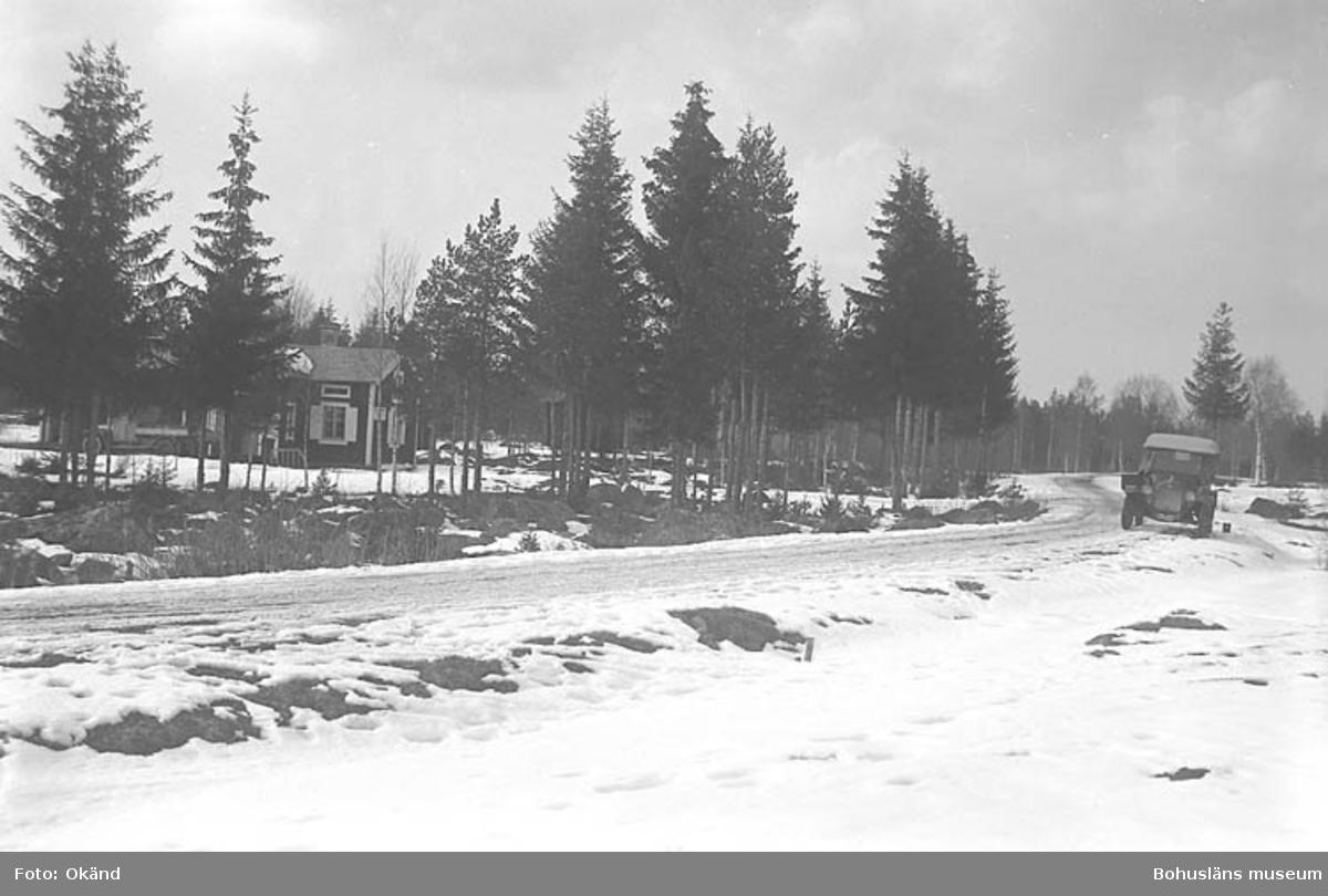 """Text till bilden: """"Hus, väg, gammal bil, vinter""""."""