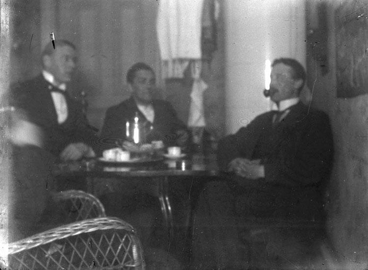 """Enl. text i blå bok: """"Interiör, tre män vid kaffebord."""" ::"""