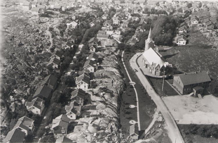 """Tryckt text på kortet: """"NORDISK FLYGTJÄNST. FLYGFOTOGRAFI N:o B 1119. Reproduktion utan vårt medgivande beivras."""". Noterat på kortet: """"GRAVARNE. Flygfoto från öster ca. 1940. Kungshamns församlingskyrkan. Invid denna löper kyrkgatan. Gatan till v. är Nygatan""""."""